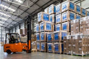 A forklift truck unloading pallets in a warehouse