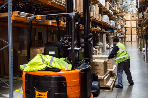 Man loading boxes onto a forklift truck at Glasswells warehouse